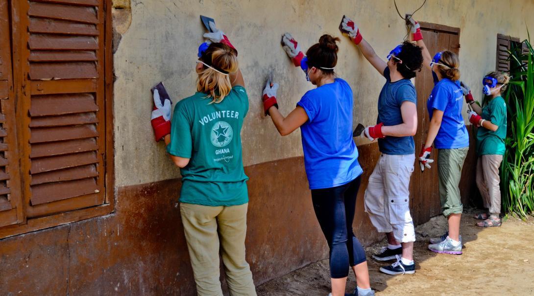 Voluntarios trabajando en labores de renovación tras elegir qué hacer en su año sabático.